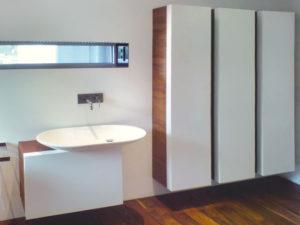 Badezimmer mit Holzmöbel und weißen Koffertüren. Im Innenraum der Türen sind kleine Regale angebracht. Das Waschbecken besticht durch seine moderne Form.