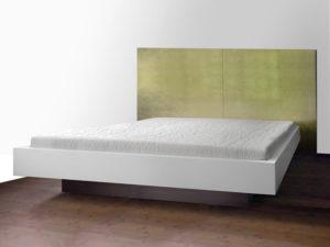 Bett mit einem mineralischen Werkstoff in Alpine weiß belegt.