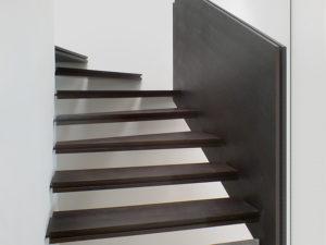 Holztreppe. Treppe Eine in der Wand überputzte Metallwange hält ein System aus mehrschichtigen Stufen.