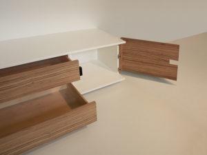Je eine Koffertüre rechts und links ermöglichen einen bequemen Zugang zum dahinter liegendem Fach, mit einem verstellbaren Fachboden. Keine vorstehenden Griffe, die Türen und Auszüge werden durch Griff in die Nut geöffnet und verringern die Verletzungsgefahr. Zwei Schubkästen in der Mitte bieten viel Platz.