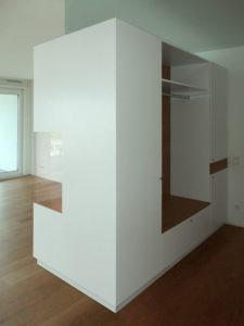 Wohnzimmer-Raumteiler, Rückseite Garderobe. Weiß lakiert in Kombination mit amerikanischem Kirschbaum.