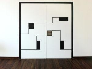 Weisse zweiflügelige Tür mit schwarzer Ornamentfräsung.